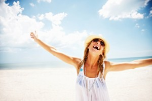 Portrait of a relaxed happy female with her arms outstretched against sky